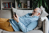 Mature man laying on sofa and reading news on his smartphone