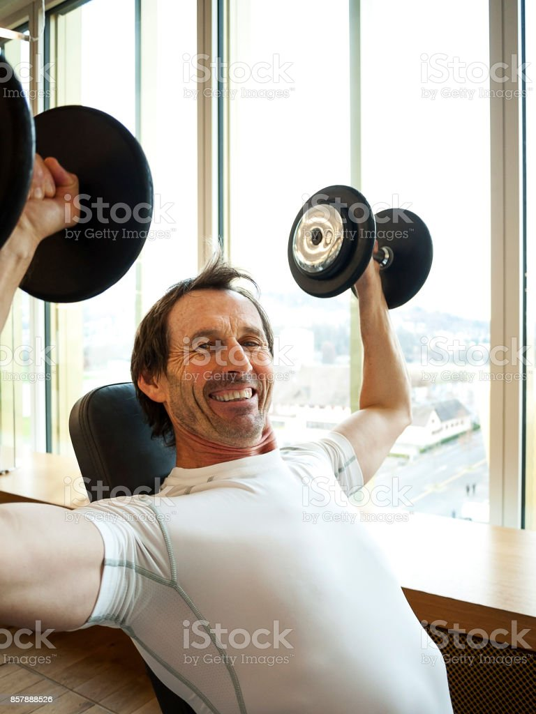 Mature Man Lifting Dumbbells stock photo