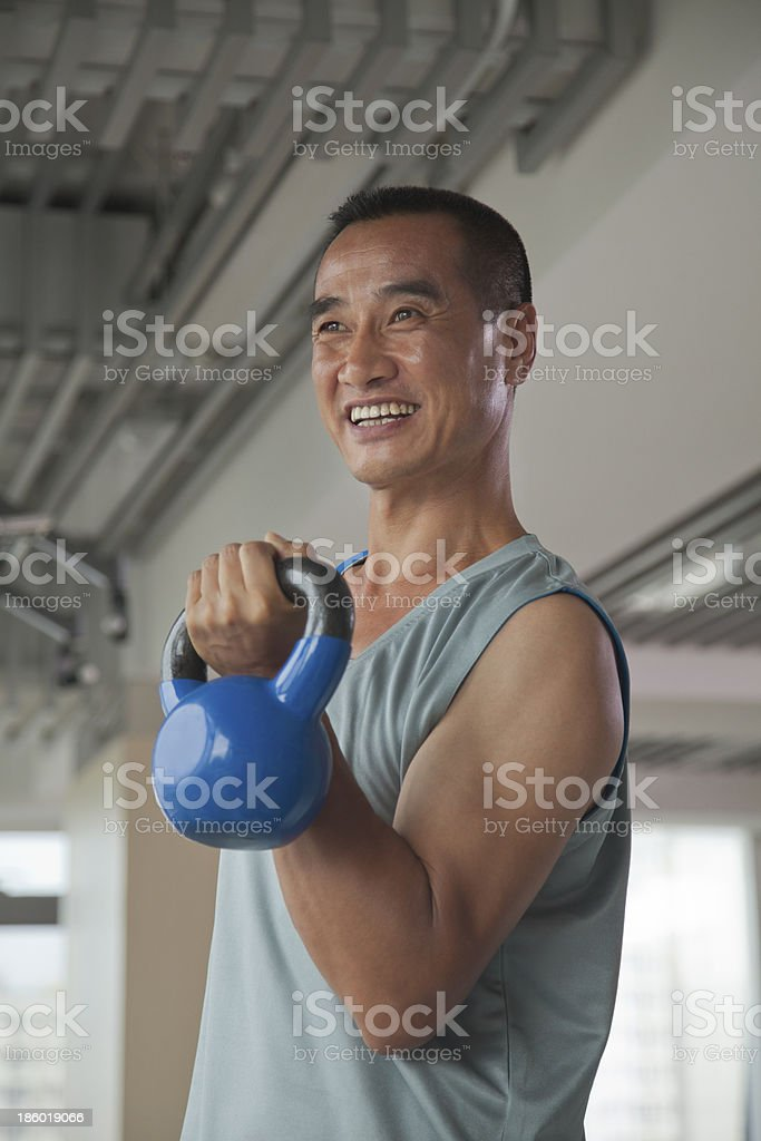 Mature man lifting weights in the gym royalty-free stock photo
