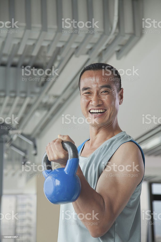 Mature man lifting weights in the gym, portrait royalty-free stock photo