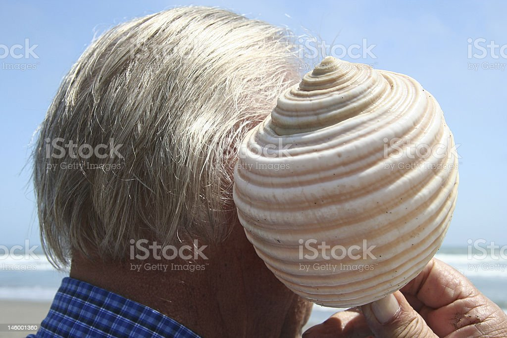 Mature man listening to a shell royalty-free stock photo