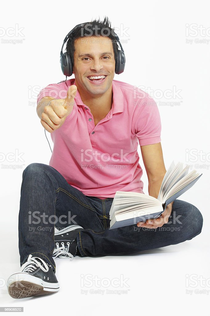 mature man listening to music and reading on white background royalty-free stock photo