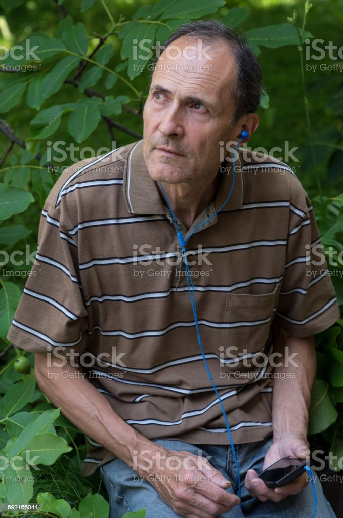 Mature man listening to the program in the garden stock photo