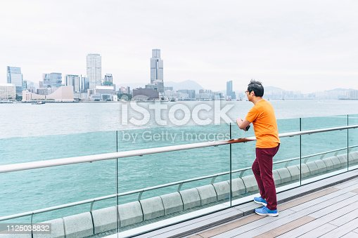 Man in his 50s in casual clothes, leaning on railing and looking at view, standing on decking, leisure, travel, solitude, contemplation