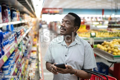 istock Mature man looking and choosing products in supermarket 1183995645