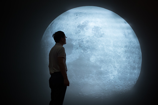 A young man is looking up at the moon, Mature Man Looking At Full Moon In Sky At Night