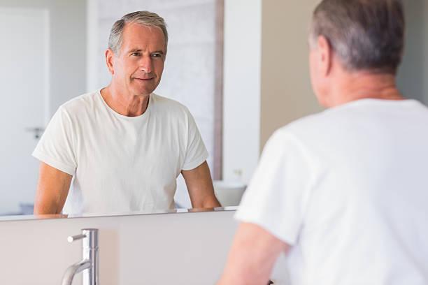 älterer mann, blick auf seine reflexion im spiegel - alte spiegel stock-fotos und bilder