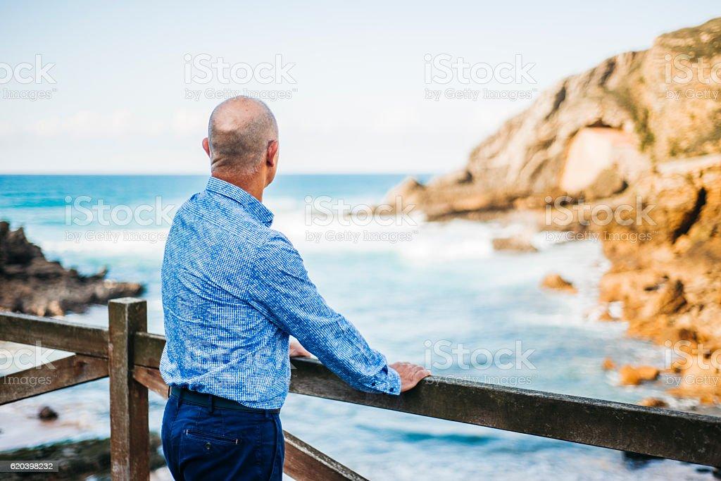 Mature man looking at the sea stock photo