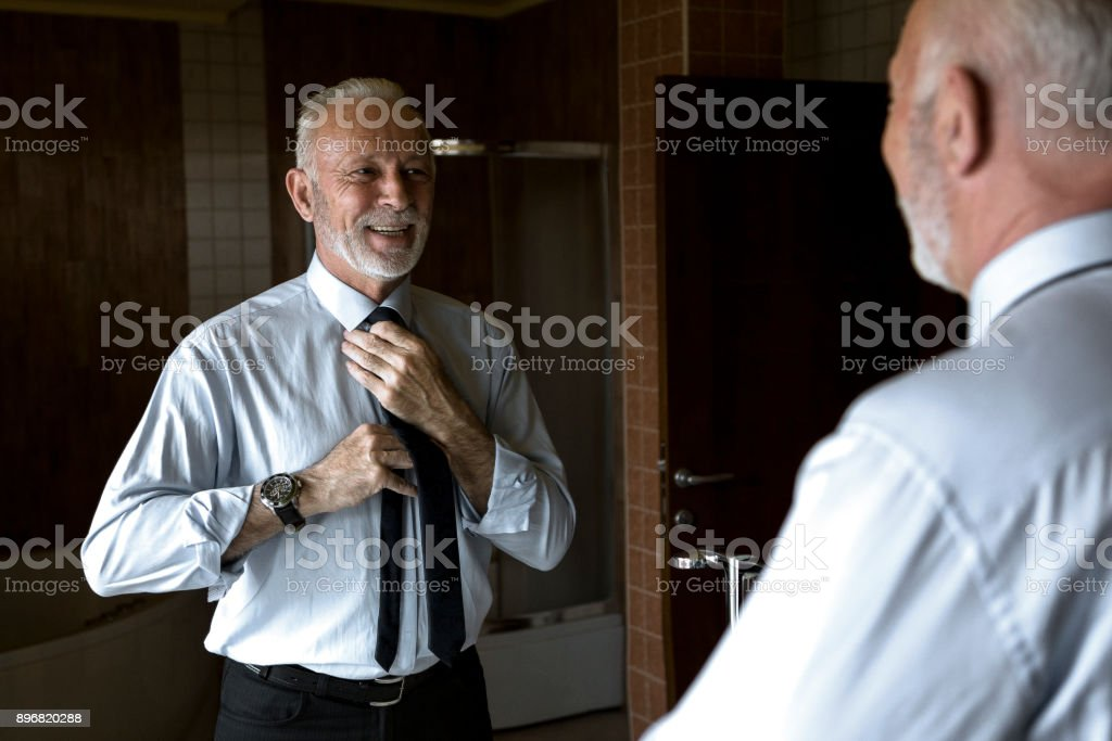 mature man looking in mirror stock photo more pictures of 50 54