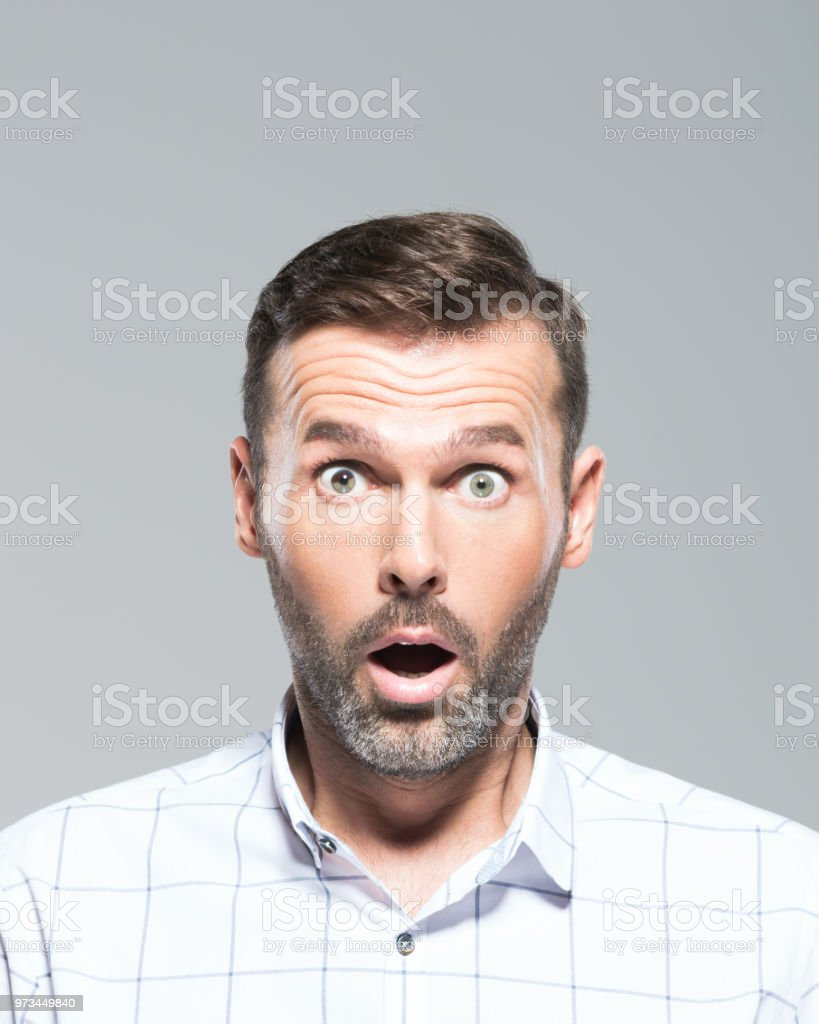 Mature man looking shocked Headshot of mature man looking shocked on grey background. Mid adult beard guy with open mouth looking at camera. 30-39 Years Stock Photo