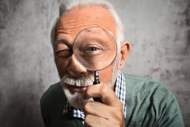 Reifer Mann schaut durch eine Lupe – Foto