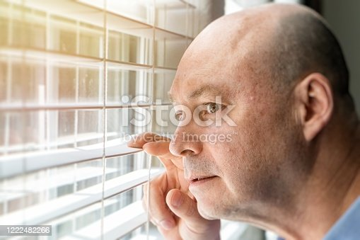 584608574 istock photo Mature man looking through a window inside his home locked down 1222482266