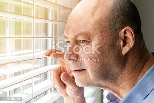 584608574 istock photo Mature man looking through a window inside his home locked down 1222483960