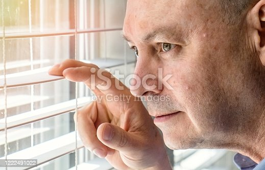 584608574 istock photo Mature man looking through a window inside his home locked down 1222491022