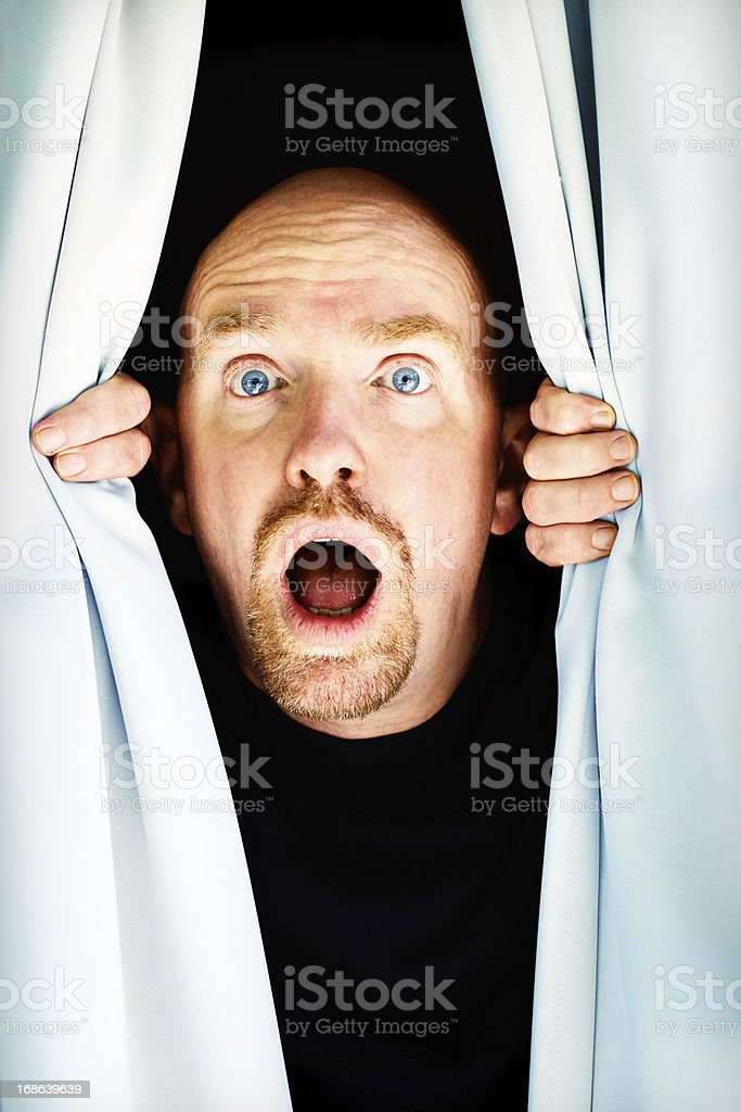 Mature man looking through curtains gasps in horror royalty-free stock photo