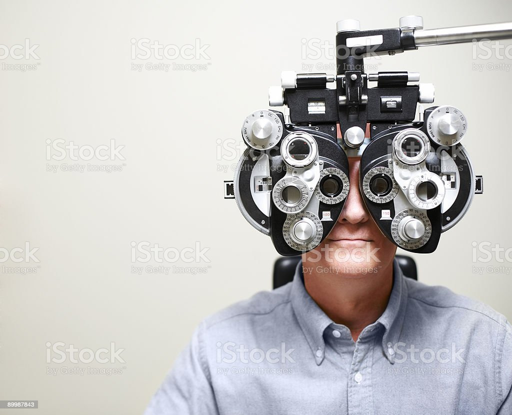 Mature Man looking through Phoroptor stock photo