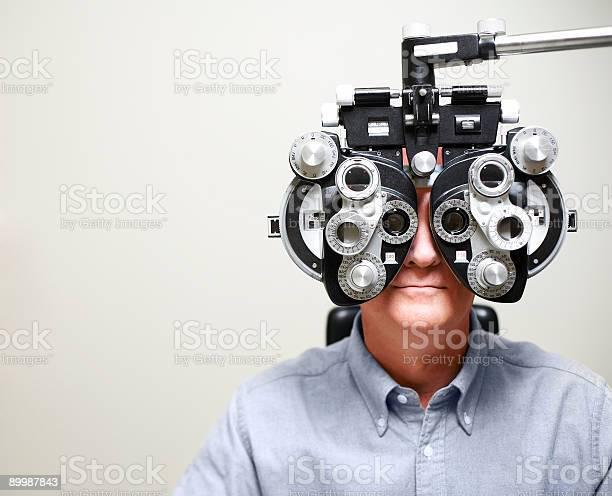 Mature Man Looking Through Phoroptor Stock Photo - Download Image Now