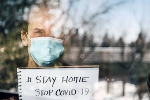 Mature man lookoineg out through window during quarantine stock photo