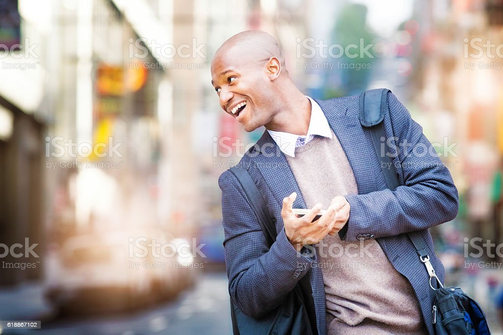 Mature man looks back smiling as he crosses the street stock photo