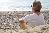 He is sitting on beach with t-shirt and pants, Liguria