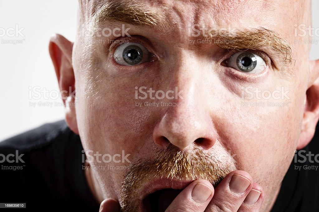 Mature man looks shocked, embarrassed, eyes wide, hand to mouth stock photo