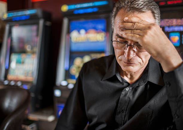 Mature man loosing his money on slot machines. Depressed man worried after loosing his money on gambling. game of chance stock pictures, royalty-free photos & images