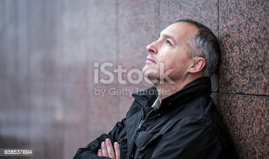 istock Mature man lost in thought standing outside and looking up 638537694