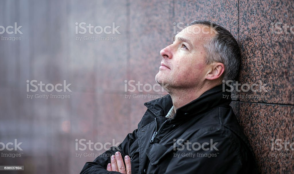 Mature man lost in thought standing outside and looking up stock photo