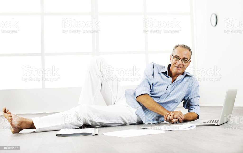 Mature man lying on floor and working royalty-free stock photo