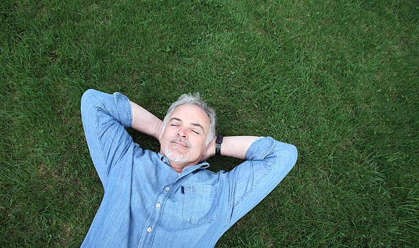 uomo maturo sdraiata sull'erba. - mani dietro la testa foto e immagini stock