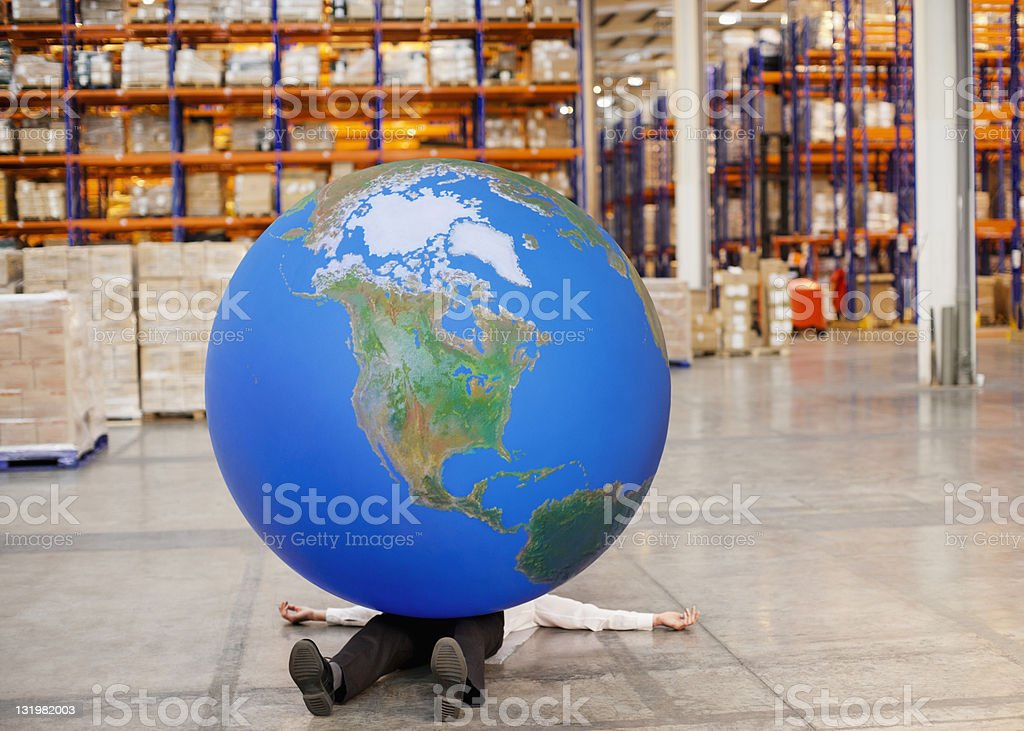 Mature man lying with large ball on top in warehouse stock photo
