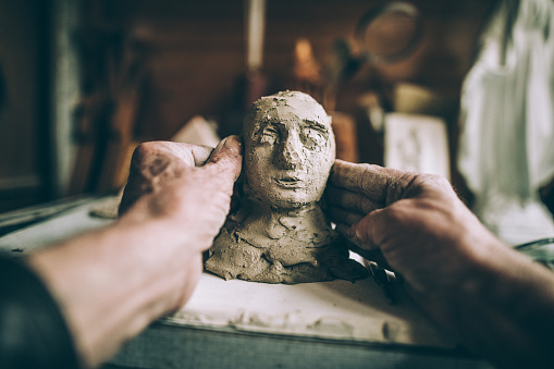 Mature man making statue of clay