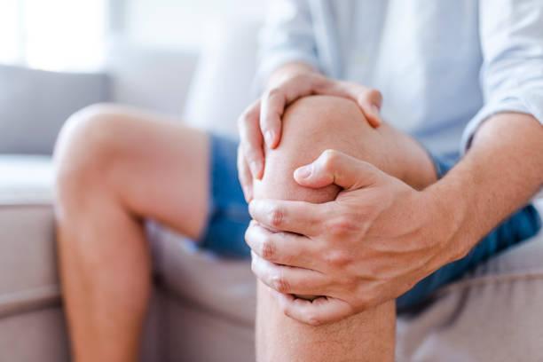 um homem maduro, massageando o joelho doloroso - articulação humana - fotografias e filmes do acervo