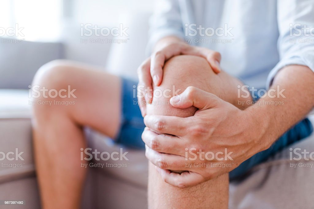 A mature man massaging his painful knee stock photo