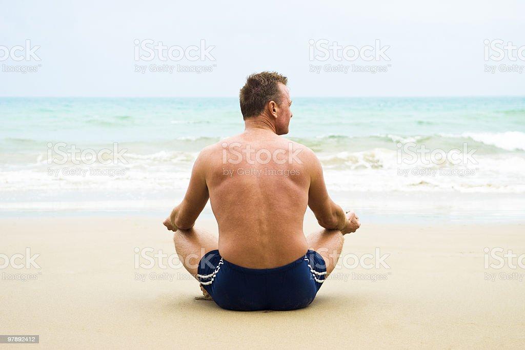 mature man meditating on the beach. royalty-free stock photo