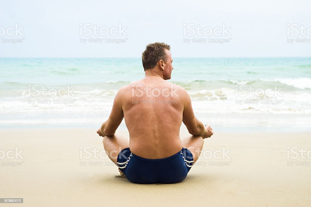 mature man meditating on the beach. stock photo