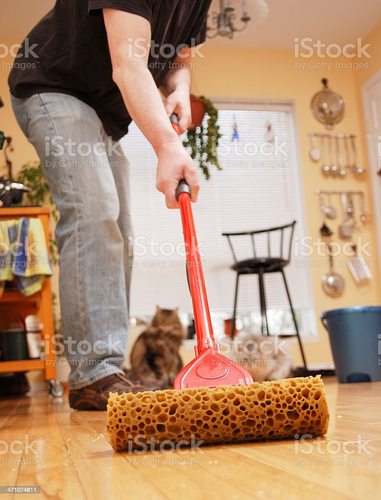 Mature Man Mopping the Kitchen Floor. royalty-free stock photo