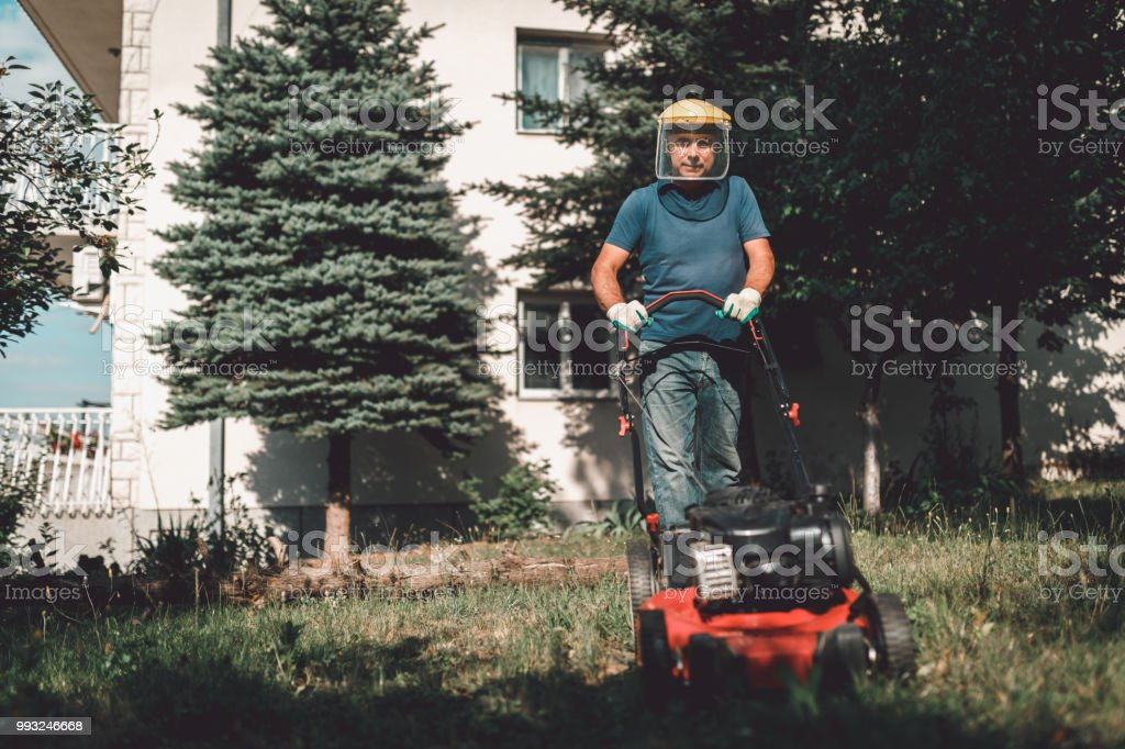 Mature man moving a lawn in the home backyard