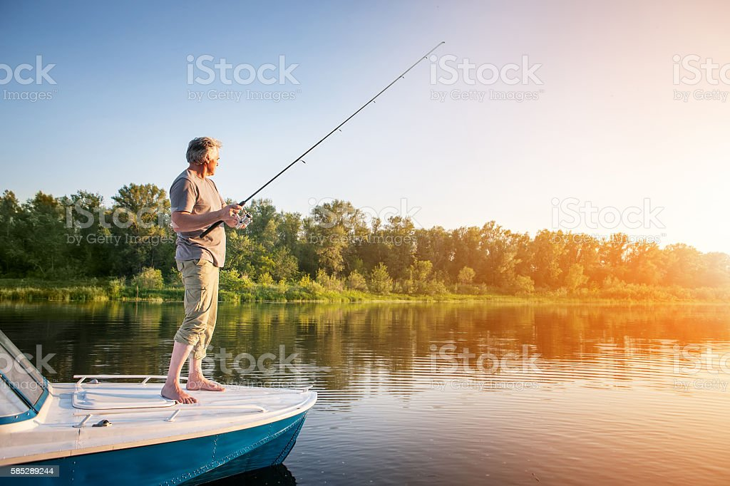 Mature man on a motor boat. Fishing stock photo