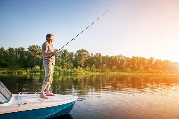 mature man on a motor boat. fishing - pescatore foto e immagini stock