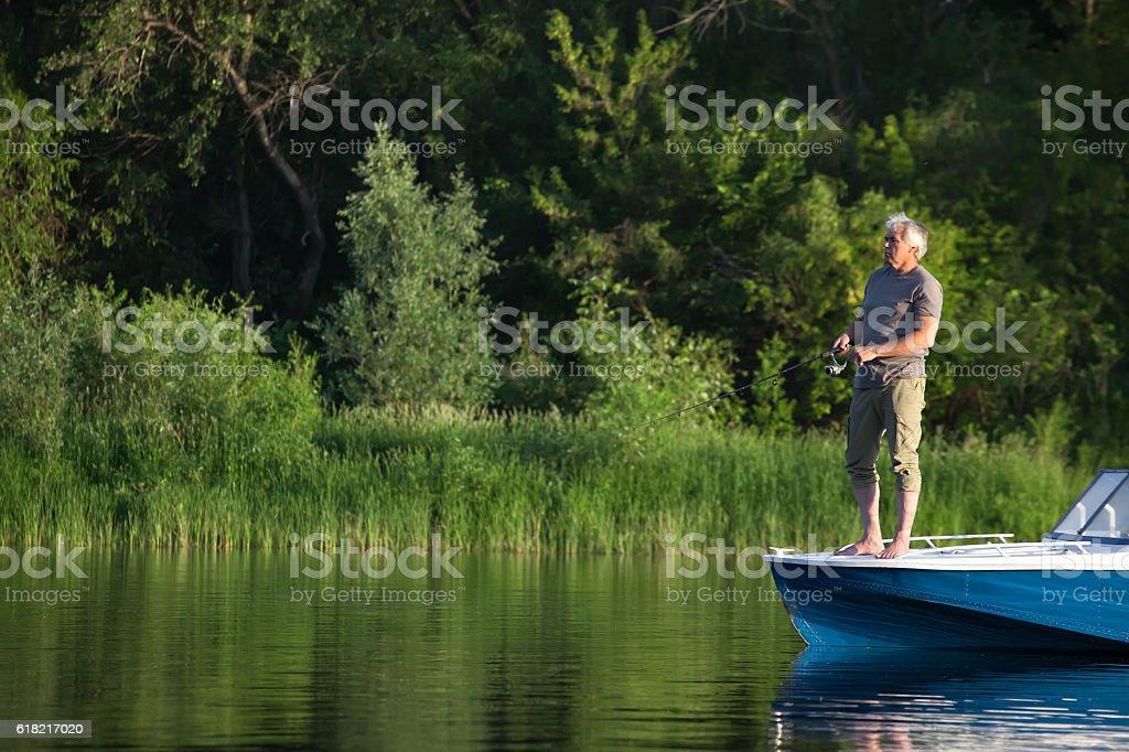 Mature man on a motor boat. Fishing. stock photo