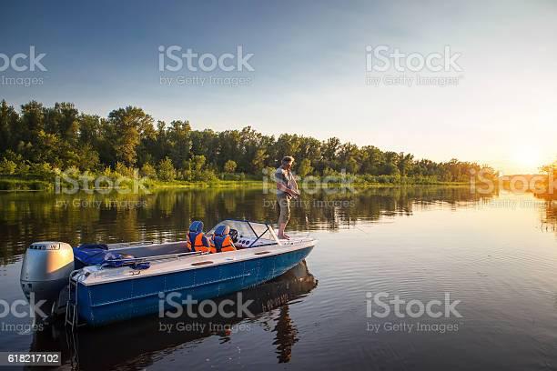 Photo of Mature man on a motor boat. Fishing.