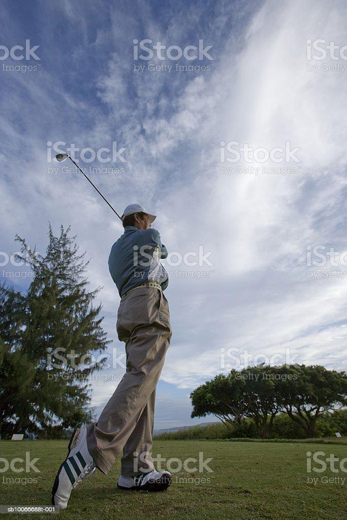 Maduro hombre jugando al golf en el campo de golf, vista de ángulo bajo de distancia, foto de stock libre de derechos