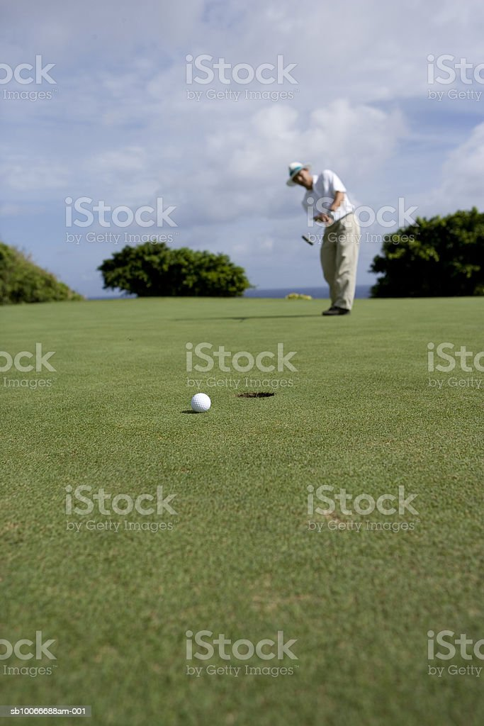 Mature man on golf course playing golf (differential focus) royalty free stockfoto