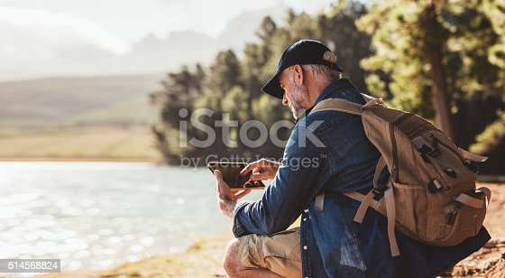 istock Mature man on hike in nature using digital tablet 514568824