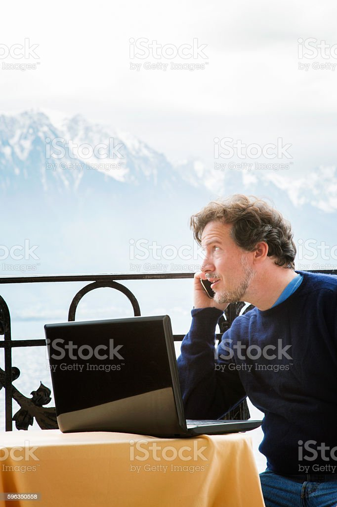 Mature man on the phone in Swiss Alps Lizenzfreies stock-foto