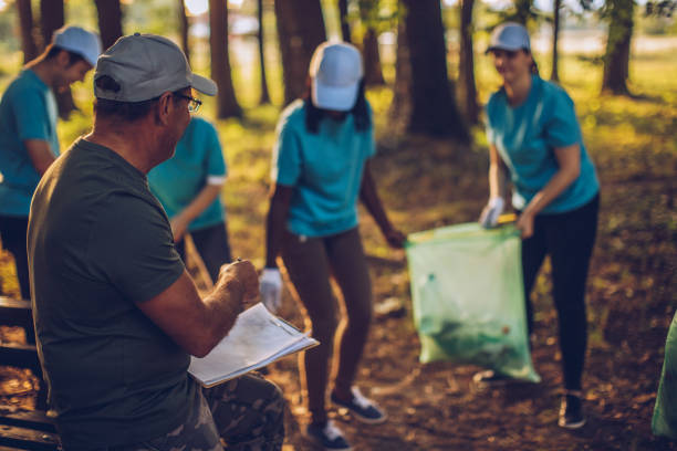 Mature man organizing volunteers to clean nature Multi-ethnic group of people, cleaning together in public park, saving the environment. social responsibility stock pictures, royalty-free photos & images