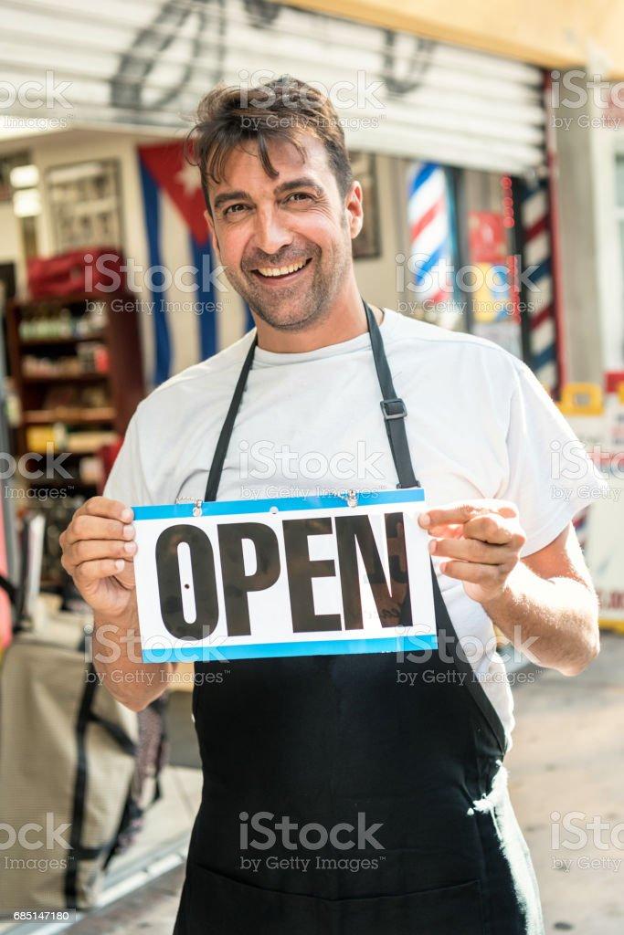 Mature man outside his business holding an open sign foto de stock libre de derechos