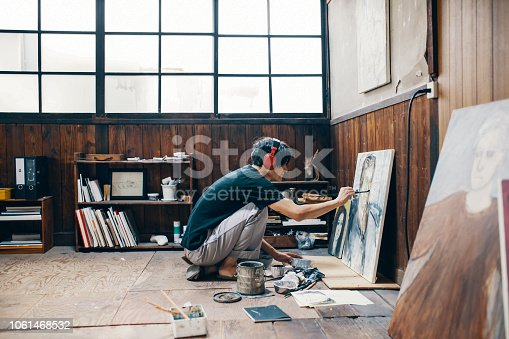 istock Mature man painting with oil paint in his studio while wearing headphones 1061468532