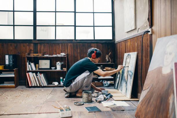 中年の男性がヘッドフォンを身に着けている間彼のスタジオで油絵絵画 - エキセントリック ストックフォトと画像